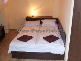 Легло в спалня на апартамента за нощувки във Варна с бяло бельо