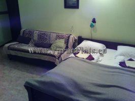 Легло и диван на едната спалня в четворната стая